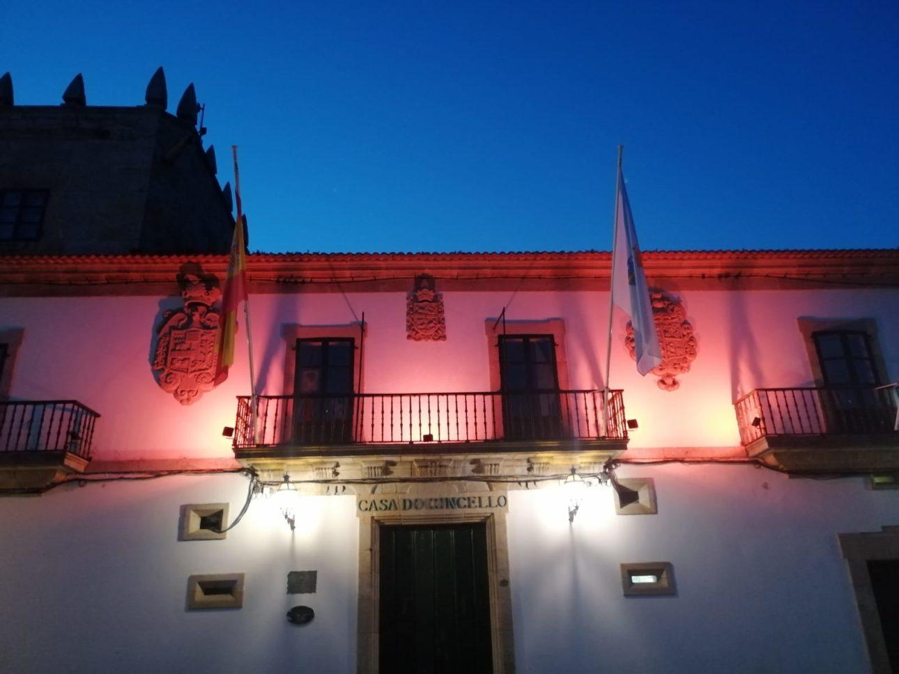 Fachada Concello de Baiona iluminada naranja scaled Baiona
